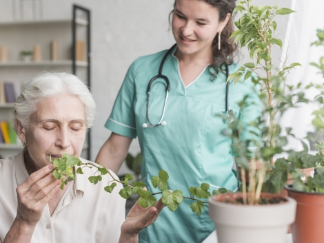 nurse-looking-at-senior-female-patient-smelling-ivy-plant-in-the-pot